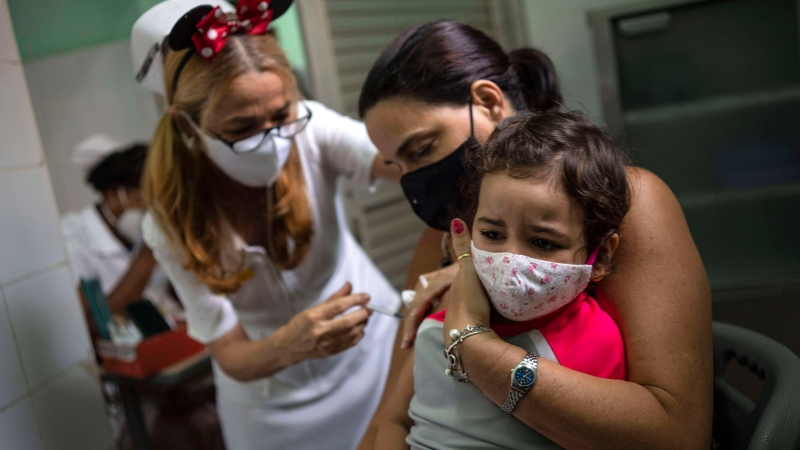 A mother holds her daughter who is injected with a dose of the Soberana-02 COVID-19 vaccine, in Havana, Cuba, Thursday, Sept. 16, 2021. (AP Photo/Ramon Espinosa)