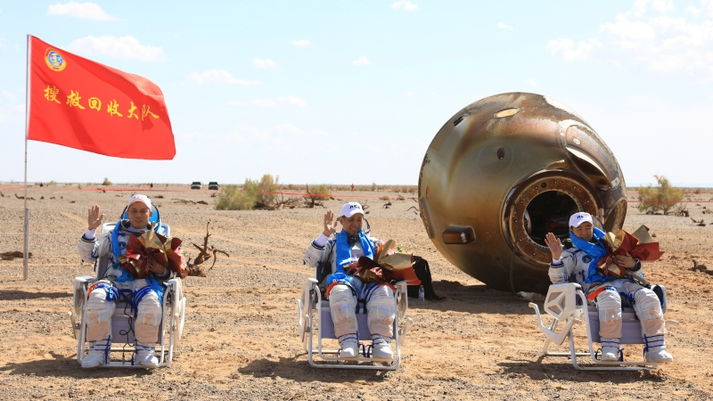 In this photo released by Xinhua News Agency, Chinese astronauts from left, Tang Hongbo, Nie Haisheng and Liu Boming wave at the Dongfeng landing site in northern China's Inner Mongolia Autonomous Region on Friday, Sept. 17, 2021. (Ju Zhenhua/Xinhua via AP)