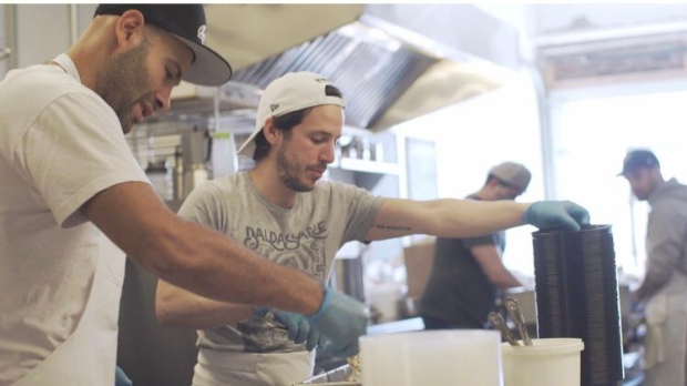 Leandro Baldassarre, owner of Famiglia Baldassarre, and James Carnevale, co-owner of Bar Ape, pack meals for Torontonians-in-need during the pandemic. Photo taken by Nick Genova.