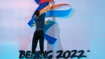 A crew member leaps to fix a logo for the 2022 Beijing Winter Olympics before a launch ceremony to reveal the motto for the Winter Olympics and Paralympics in Beijing, Friday, Sept. 17, 2021. (AP Photo/Mark Schiefelbein)
