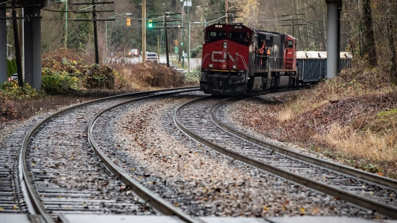 A CN rail worker stands on an idle locomotive as protesters opposed to the Trans Mountain pipeline expansion block rail lines, in Burnaby, B.C., on Nov. 27, 2020. (Darryl Dyck / THE CANADIAN PRESS)