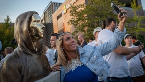 A woman takes a selfie with a newly unveiled statue of the mysterious developer of the Bitcoin digital currency in Budapest, Hungary, on Sept. 16, 2021.  (Bela Szandelszky / AP)