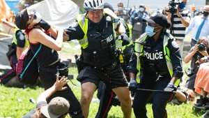 Police remove encampment supporters as they clear Lamport Stadium Park encampment in Toronto on Wednesday July 21, 2021. The operation came a day after a different encampment was cleared at a downtown park. The city has cited the risk of fires and the need to make parks accessible to everyone as factors behind the clearings. THE CANADIAN PRESS/Chris Young