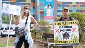An anti-vaccine protester and a vaccine supporter demonstrate in from of a hospital in Montreal, on Monday, September 13, 2021. THE CANADIAN PRESS/Paul Chiasson