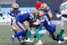 Winnipeg Blue Bombers' Jonathan Kongbo (2) and Alden Darby (22) sack Saskatchewan Roughriders quarterback Isaac Harker (16) during the second half of CFL action in Winnipeg Saturday, September 11, 2021.THE CANADIAN PRESS/John Woods