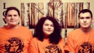Ailah Carpenter (centre) and her brothers pose in the orange shirts she designed. (Ailah Carpenter/Submitted)