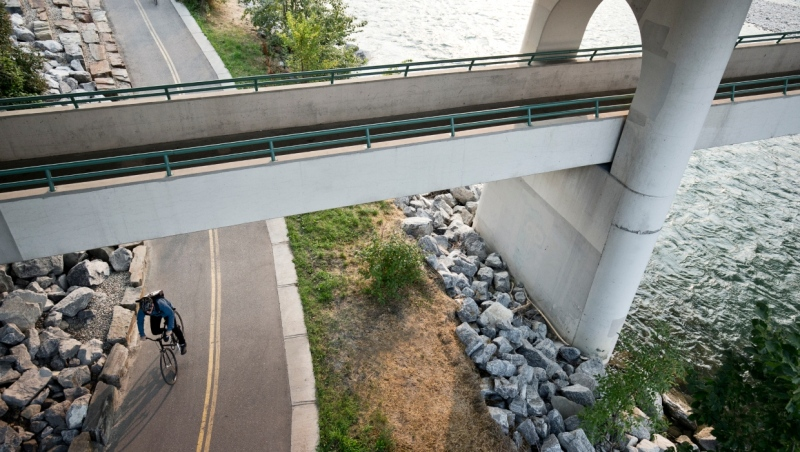 A cyclist rides on a path near the river in Calgary. (Getty Images)