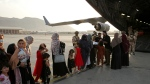 FILE - Afghans prepare to to be evacuated aboard a Qatari transport plane, at Hamid Karzai International Airport in Kabul, Afghanistan, August, 18, 2021. (Qatar Government Communications Office via AP)