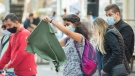 A woman wears a face mask as she browses at a clothing stall set out for a sidewalk sale on Ste-Catherine Street in Montreal, Sunday, September 12, 2021, as the COVID-19 pandemic continues in Canada and around the world. THE CANADIAN PRESS/Graham Hughes