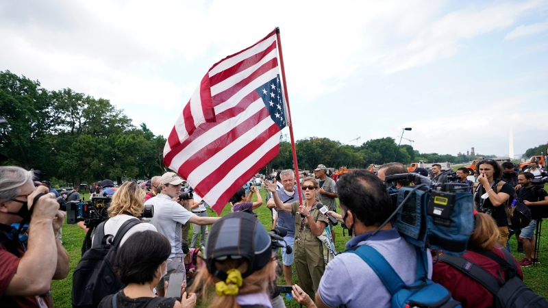 """A woman holds an upside down American flag as she speaks with members of the media before a rally near the U.S. Capitol in Washington, Saturday, Sept. 18, 2021. The rally was planned by allies of former President Donald Trump and aimed at supporting the so-called """"political prisoners"""" of the Jan. 6 insurrection at the U.S. Capitol. (AP Photo/Brynn Anderson)"""