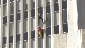 A firefighter repels down the east side of City Hall to reach the practice dummy. (David Prisciak/CTV News)