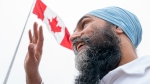 NDP leader Jagmeet Singh walks past a Canadian flag as he visits the waterfront in Dartmouth, N.S., Friday, September 17, 2021. THE CANADIAN PRESS/Jonathan Hayward