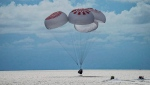 In this image taken provided by SpaceX, a capsule carrying four people parachutes into the Atlantic Ocean off the Florida coast, Saturday, Sept. 18, 2021. (SpaceX via AP)
