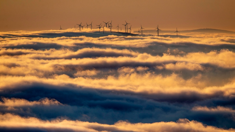 In this Jan. 6, 2020, file photo wind turbines stand on a hill and are surrounded by fog and clouds in the Taunus region near Frankfurt, Germany. (AP Photo/Michael Probst, File)