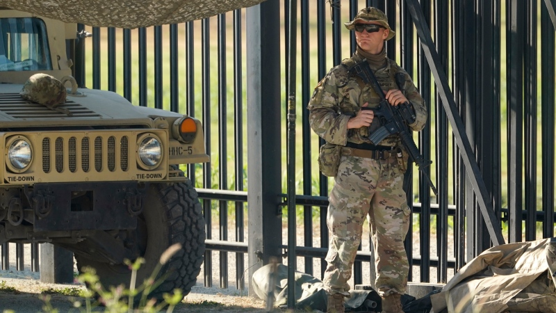 U.S. National Guardsmen stand watch at a gate along a fence near the International bridge where thousands of Haitian migrants have created a makeshift camp, Sunday, Sept. 19, 2021, in Del Rio, Texas. (AP Photo/Eric Gay)