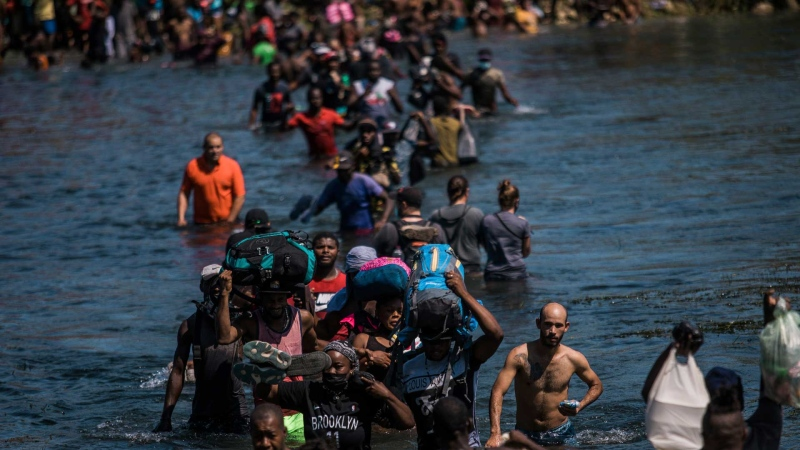 Migrants wade across the Rio Grande from Del Rio, Texas to Ciudad Acuna, Mexico, to shop for food and supplies before returning back to the US side of the border, Sunday, Sept. 19, 2021. (AP Photo/Felix Marquez)