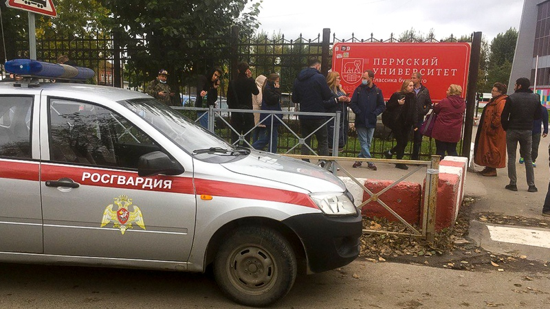 People stand behind the fence near the Perm State University with the a Posguardia (National Guardia) on the left, in Perm, Russia, Monday, Sept. 20, 2021. (AP Photo/Anastasia Yakovleva)