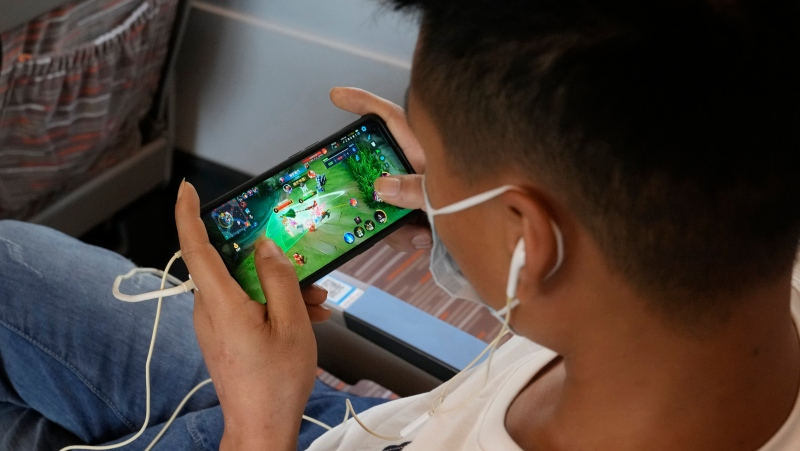 A man plays the popular Honor of Kings online game from Chinese gaming platform Tencent during a high speed train from Henan to Beijing Wednesday, Sept. 15, 2021. (AP Photo/Ng Han Guan)