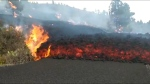 Lava spews, flows over road as volcano erupts