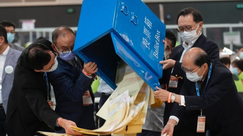 Erick Tsang, second left, Secretary for Constitutional and Mainland Affairs Bureau, helps officials pour out ballots from a box at a counting center in Hong Kong, Sunday, Sept. 19, 2021. (AP Photo/Vincent Yu)