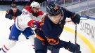 Edmonton Oilers' Kailer Yamamoto (56) is checked by Montreal Canadiens' Phillip Danault (24) during second period NHL action in Edmonton on Wednesday, April 21, 2021.THE CANADIAN PRESS/Jason Franson