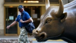A man wearing a mask passes the Charging Bull statue in New York's financial district, on Sept. 8, 2020. (Mark Lennihan / AP)