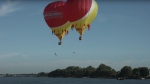 Quebec divers Lysanne Richard and Yves Milord have set a world record after performing a synchronized high dive from two hot air balloons. (International de montgolfières de Saint-Jean-sur-Richelieu)