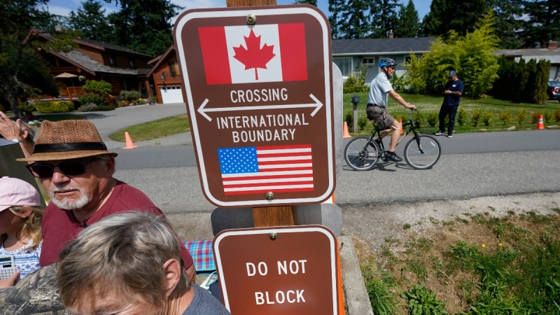 A family visits across the U.S.-Canada border at the Peace Arch Historical State Park in Blaine, Wash., as a cyclist rides past on the Canadian side, on Aug. 9, 2021. (Elaine Thompson / AP)