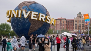 People take selfies with an icon near the entrance to Universal Studios Beijing, on Sept. 20, 2021.  (Andy Wong / AP)
