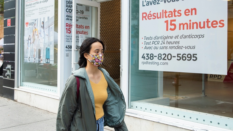 A woman wears a face mask as she walks by a COVID-19 rapid testing clinic in Montreal, Sunday, September 12, 2021, as the COVID-19 pandemic continues in Canada and around the world. THE CANADIAN PRESS/Graham Hughes