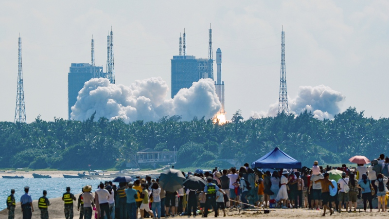 In this photo released by Xinhua News Agency, people watch the Long March-7 Y4 carrier rocket carrying Tianzhou-3 cargo spacecraft lift off from the Wenchang Space Launch Center in Wenchang in southern China's Hainan Province, Monday, Sept. 20, 2021. (Zhou Jiayi/Xinhua via AP)