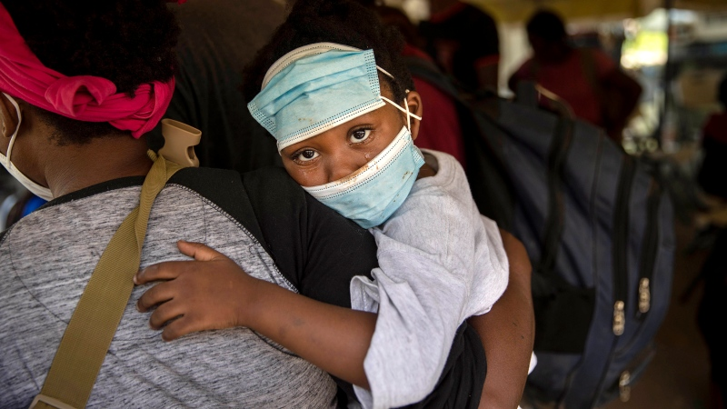 A little girl with teary eyes is carried by a woman who was deported from the U.S. border with Mexico at Toussaint Louverture International Airport in Port-au-Prince, Haiti, Monday, Sept. 20, 2021. The U.S. is flying Haitians camped in a Texas border town back to their homeland. (AP Photo/Joseph Odelyn)