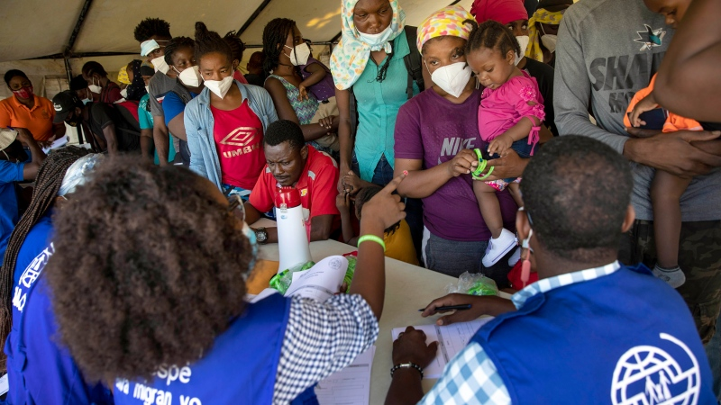 Haitians who were deported from the U.S. border with Mexico are attended to by members of the IOM UN Migration organization before they get tested for COVID-19 at Toussaint Louverture International Airport in Port-au-Prince, Haiti, Monday, Sept. 20, 2021. (AP Photo/Joseph Odelyn)