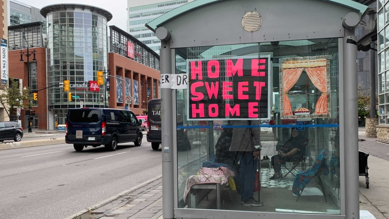 A group of Winnipeggers set up a living space inside a bus shelter to raise awareness about homelessness. (Source: CTV News/Jamie Dowsett)