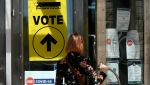 A person passes posters advising measures against COVID-19 as they enter Ottawa City Hall, a polling location on election day, Sept. 20, 2021. THE CANADIAN PRESS/Justin Tang
