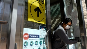 A person passes posters advising measures against COVID-19 as they leave Ottawa City Hall, a polling location, on election day during the 44th Canadian general election, on Monday, Sept. 20, 2021. (Justin Tang /THE CANADIAN PRESS)