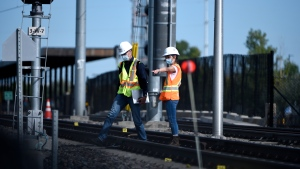 Workers wearing a hard hats from train manufacturer Alstom work among evidence markers laid on the tracks Monday, Sept. 20, 2021 after an OC Transpo O-Train derailed west of Tremblay LRT Station on Sunday in Ottawa. (Justin Tang /THE CANADIAN PRESS)