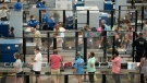 FILE - Travellers wear face coverings in the queue for the north security checkpoint in the main terminal of Denver International Airport Tuesday, Aug. 24, 2021, in Denver. (AP Photo/David Zalubowski)
