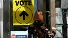 A person passes posters advising measures against COVID-19 as they enter Ottawa City Hall, a polling location, on election day during the 44th Canadian general election, on Monday, Sept. 20, 2021. THE CANADIAN PRESS/Justin Tang