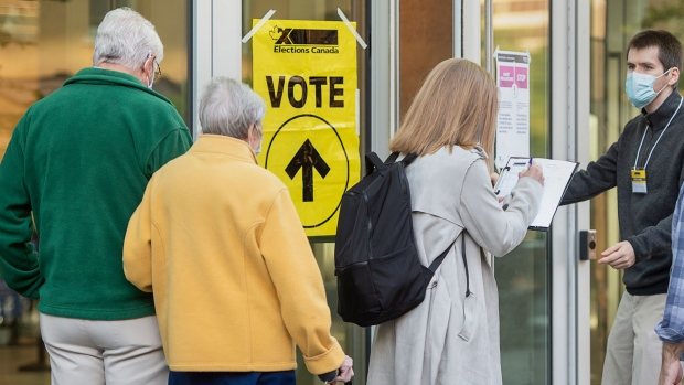 A voter provides COVID-19 contact-tracking information at the Halifax Convention Centre as they prepare to vote in the federal election in Halifax on Monday, Sept. 20, 2021. THE CANADIAN PRESS/Andrew Vaughan
