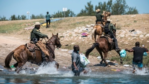 U.S. Customs and Border Protection mounted officers attempt to contain migrants as they cross the Rio Grande from Ciudad Acuña into Del Rio, Texas, Sunday, Sept. 19, 2021. (AP Photo/Felix Marquez)