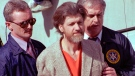 In this April 4, 1996 file photo Theodore John Kaczynski is flanked by federal agents as he is led to a car from the federal courthouse in Helena, Mont. (AP Photo/John Youngbear, File)