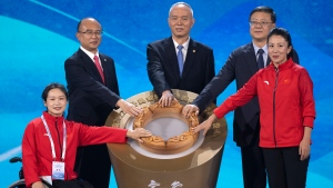 Cai Qi, center, Beijing Communist Party secretary, Chen Jining, second from right, Beijing mayor and executive president of the Beijing 2022 Organizing Committee, and other dignitaries prepare to reveal the motto for the 2022 Beijing Winter Olympics and Paralympics at a launch ceremony in Beijing, Friday, Sept. 17, 2021. (AP Photo/Mark Schiefelbein)