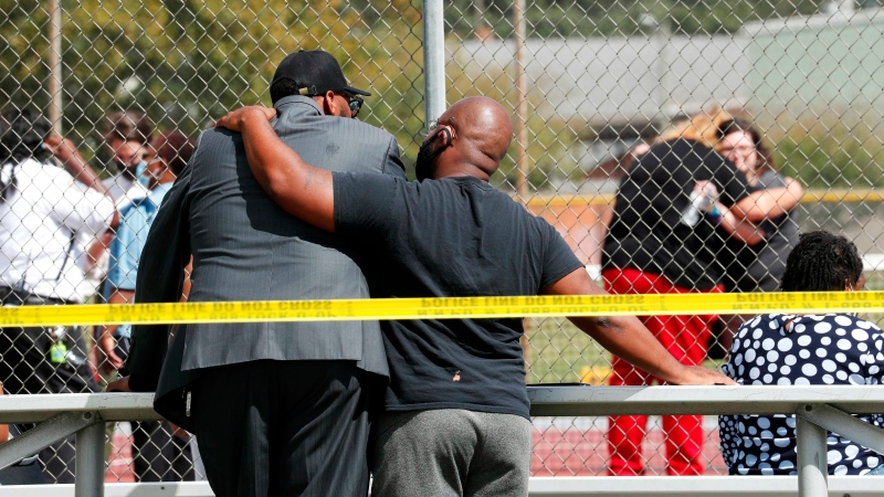 People console one another outside Heritage High School, near the tennis courts, following a shooting at the school, Monday, Sept. 20, 2021, in Newport News, Va. (Jonathon Gruenke/The Virginian-Pilot via AP)