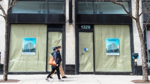 Pedestrians walk past a closed business Friday April 24, 2020 in Montreal. THE CANADIAN PRESS/Ryan Remiorz