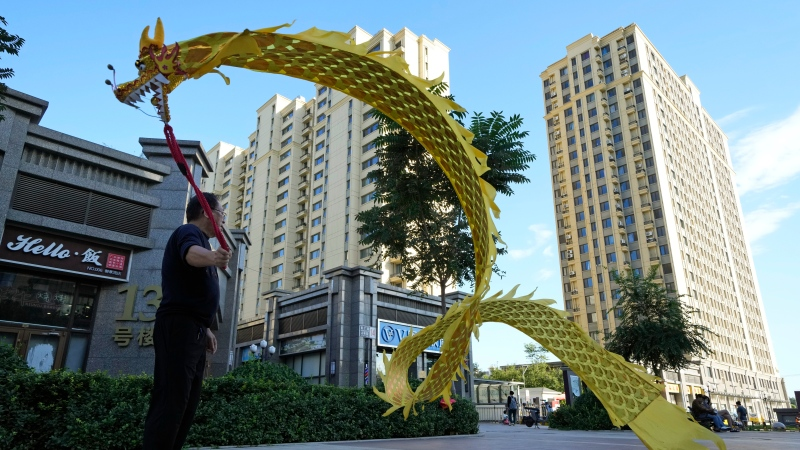 A resident wields a cloth dragon outside the Evergrande Yujing Bay residential complex in Beijing, China, Tuesday, Sept. 21, 2021. (AP Photo/Ng Han Guan)