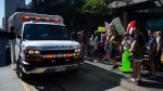 An ambulance makes its way down the street during a demonstration to protest measures taken by public health authorities to curb the spread of COVID-19, in Toronto, Saturday, Sept. 18, 2021. THE CANADIAN PRESS/Chris Young