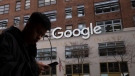 A man using a mobile phone walks past Google offices in New York, on Dec. 17, 2018. (Mark Lennihan / AP)