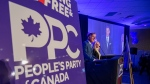 People's Party of Canada Leader Maxime Bernier and wife Catherine Letarte speaks from a podium to supporters during the PPC headquarters election night event in Saskatoon, Sask., Monday, Sept. 20, 2021. THE CANADIAN PRESS/Liam Richards