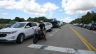 Vehicles from members of the media and curious passersby line a road outside the entrance of the Carlton Reserve during a search for Brian Laundrie, Tuesday, Sept. 21, 2021, in Venice, Fla. (AP Photo/Phelan M. Ebenhack)